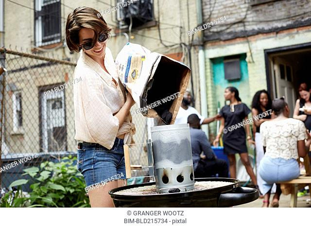 Woman pouring charcoal onto grill at barbecue