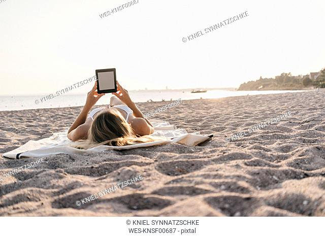 Young woman lying on blanket on the beach using tablet
