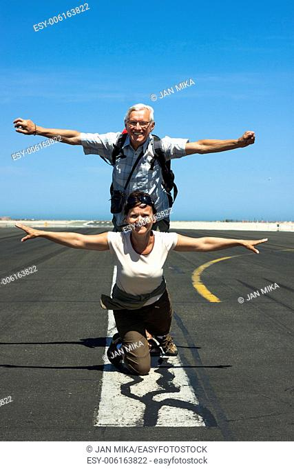 Happy senior man and middle aged woman imitating airplane at the airport runway