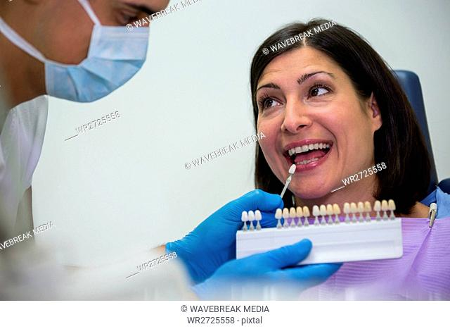 Dentist examining female patient with teeth shades