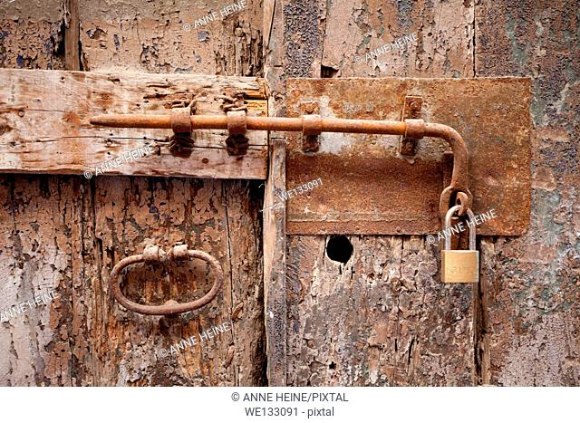 Old door with door knob and modern lock, Cagliaria, Sardinia, Italy