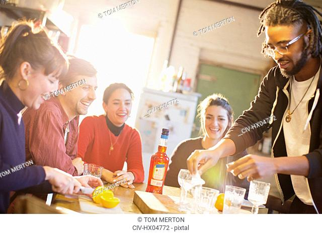 Young adult friends making cocktails at kitchen table
