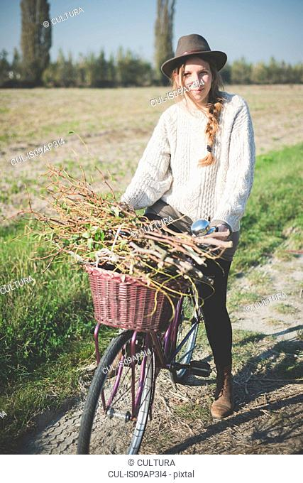 Young woman carrying bunch of sticks on bicycle