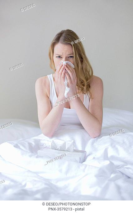 Woman sick with handkerschiefs in bed
