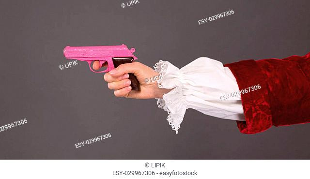Close-up of pink plastic gun over grey background. Woman's hand holding child's toy in studio