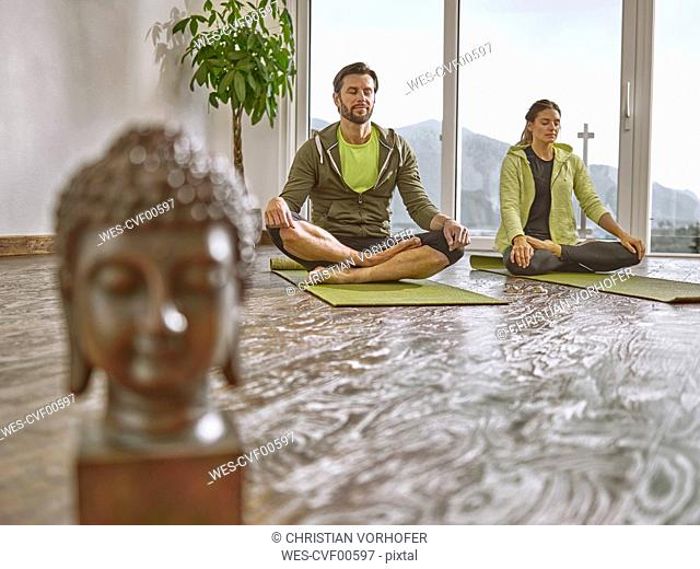 Couple practicing yoga in a room with panorama window