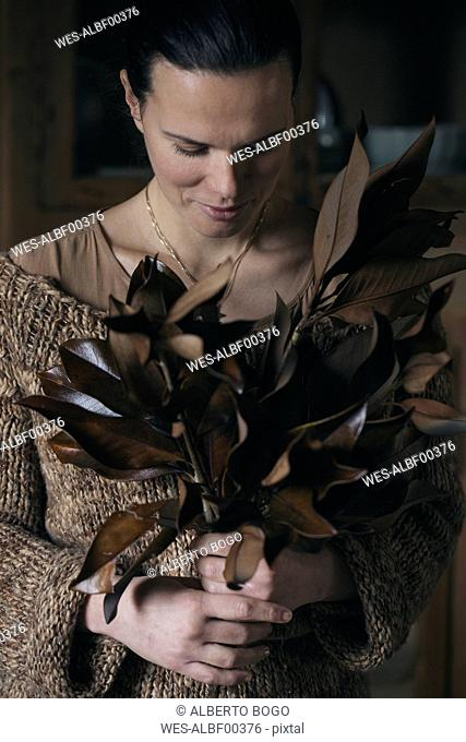 Woman with bunch of twigs with brown leaves