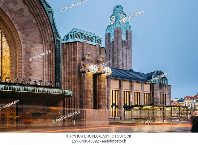 Helsinki, Finland. Night View Of Statues On Entrance To Helsinki Central Railway Station. Evening Or Night Illumination