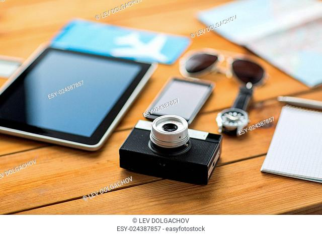 travel, tourism, technology and objects concept - close up of retro film camera, gadgets and personal stuff