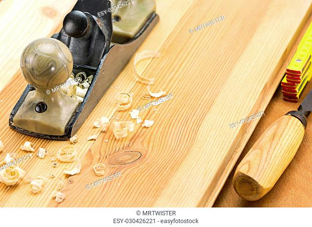 Carpenter's plane and tools with shaving on wooden boards