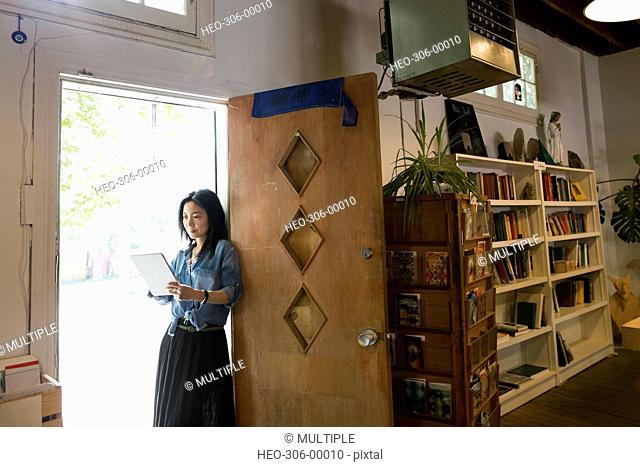 Female shop owner using digital tablet in bookshop doorway