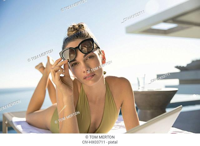 Portrait serious, confident woman in bathing suit and sunglasses sunbathing with digital tablet on sunny luxury patio