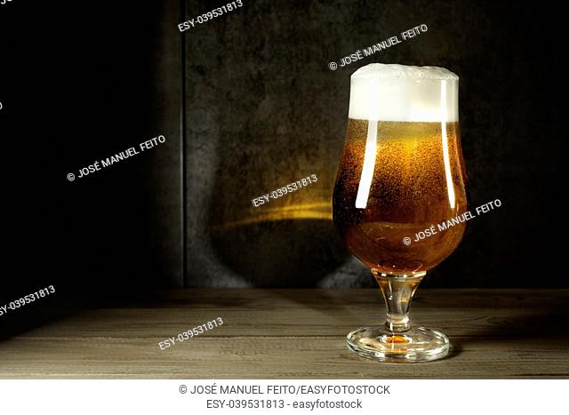 Ale beer cup with foam on wood table and metallic background in twilight and reflection