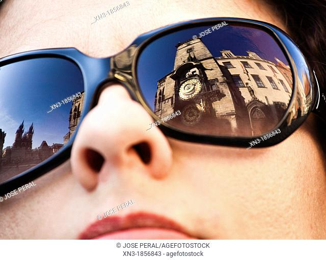 Reflected in women with glasses: Astronomical clock, Old Town Hall, at left Church of Mother of God before Týn or Church of Our Lady before Tyn, Old Town Square
