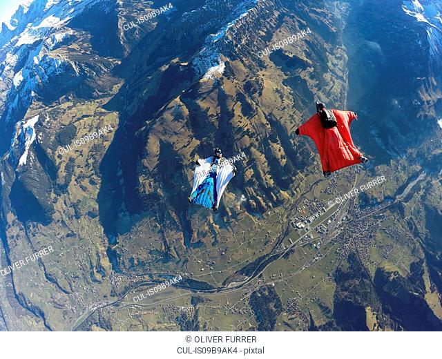 Aerial view of two wingsuit flyers, one on his back facing one in red suit flying above landscape
