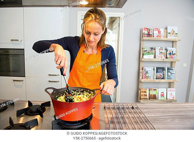 Kaatsheuvel, Netherlands. Mid adult woman stirring a red colored saucepan on her stove, busy making a Lasagna dish dinner