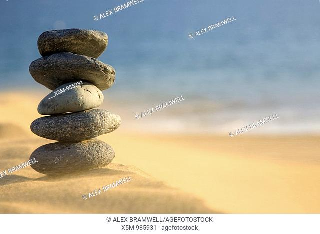 Stack of volcanic pebbles on a beach with blowing sand