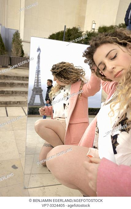 woman turned away from her mirror image in city near tourist sight Eiffel Tower, at Espl. du Trocadéro, in Paris, France
