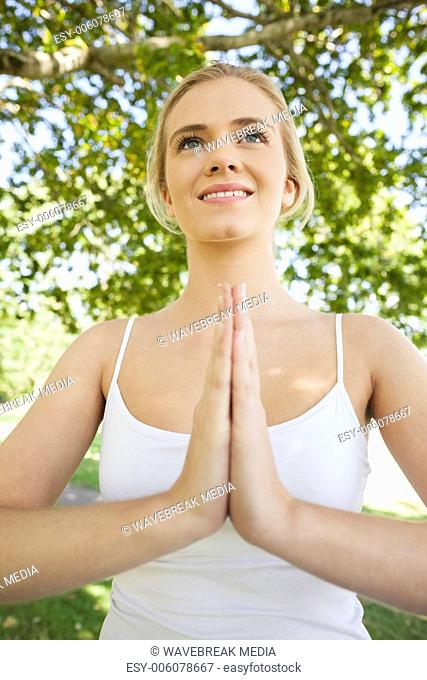 Front view of young woman meditating in sukhasana pose