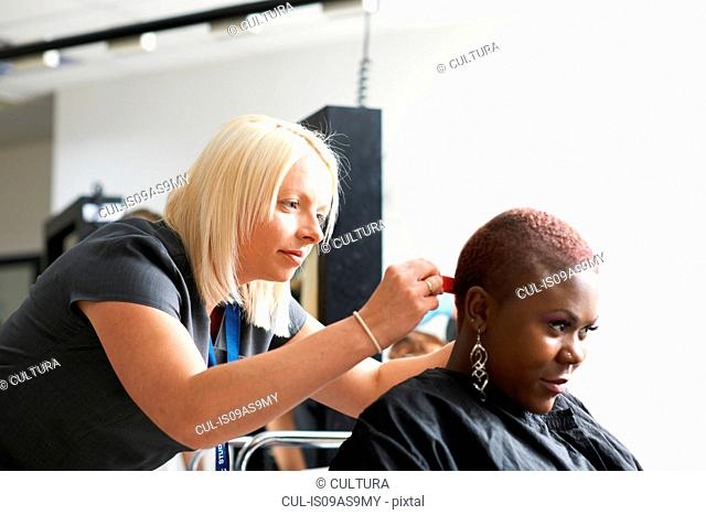 Side view of hairdresser and young woman wearing hair cutting cape in hair salon looking down