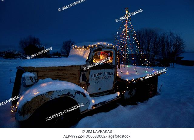 Chevy flatbed truck with Christmas lights and Snowman in driver's seat in Homer,Kenai Peninsula, Southcentral Alaska, Winter