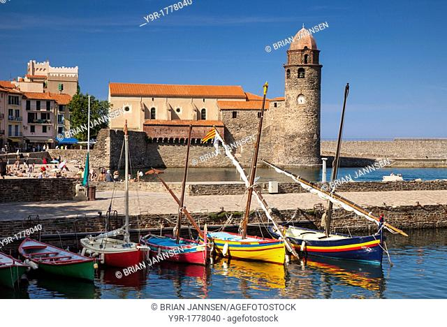 Colorful boats and vacationing swimmers below Eglise Notre Dame des Anges Church, Collioure, Languedoc-Roussillon, France