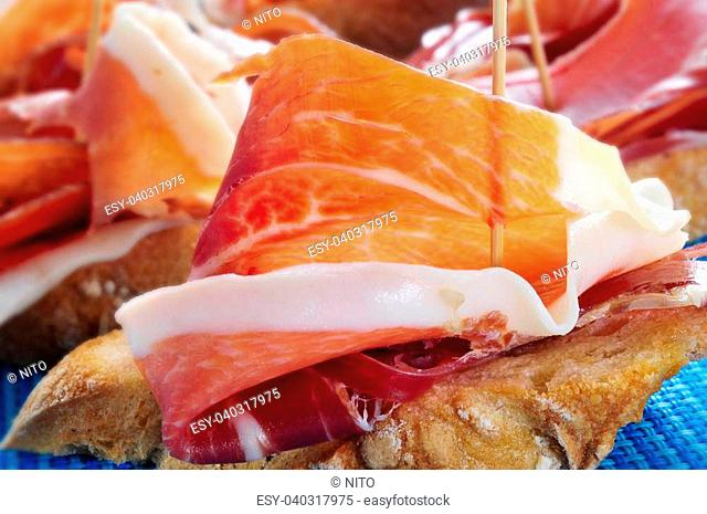 closeup of a plate with some typical spanish pinchos de jamon, serrano ham served on bread as tapas