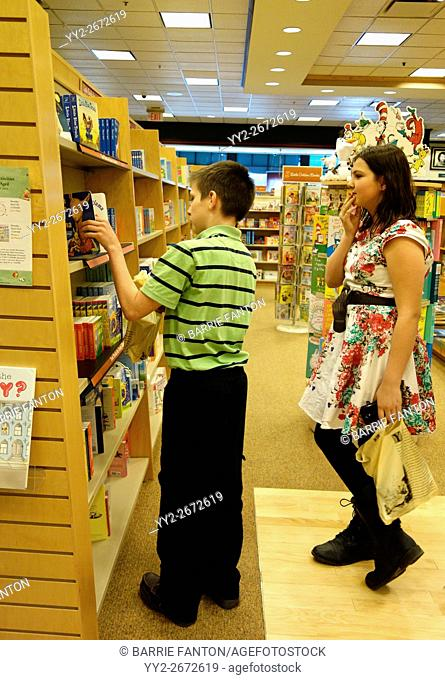 Preteen Girl and Boy Browsing in Book Store, Rochester, New York, USA