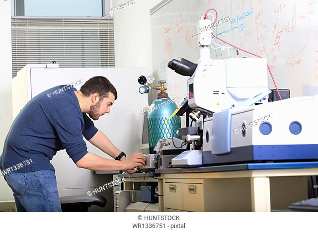 Engineering student setting adjustment dials for chemical analysis equipment in a laboratory