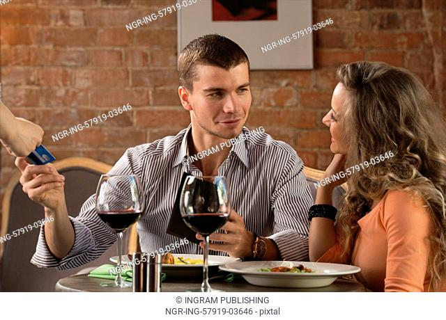 Happy couple in restaurant pay cash free by credit card electronic security money