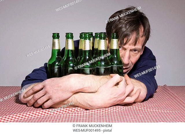Man at table surrounded by beer bottles