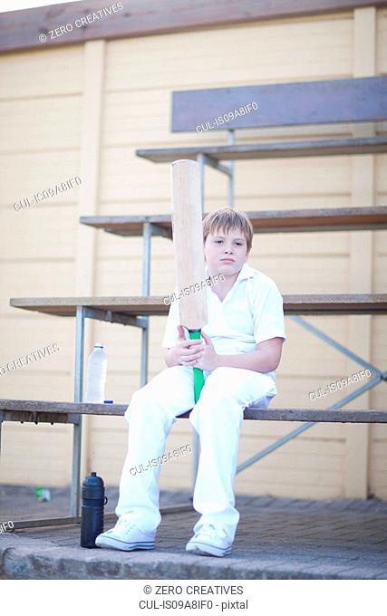 Boy holding cricket bat sitting on bleachers