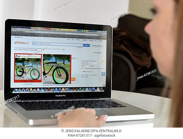 ILLUSTRATION - A young woman browses on her notebook computer through the web page of Chinese online retailer Alibaba looking at bicycles on sale in Berlin