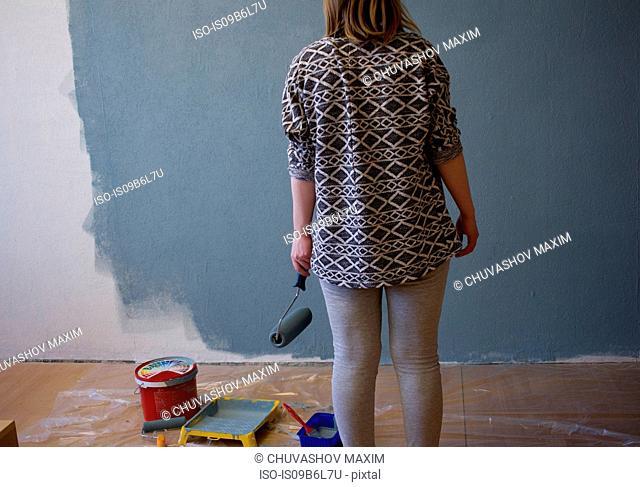 Rear view of young woman looking at part grey painted interior wall at home