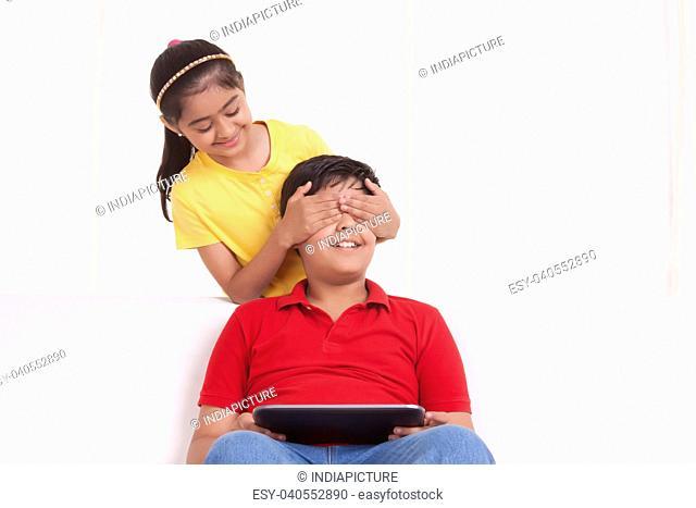 Girl covering boys eyes
