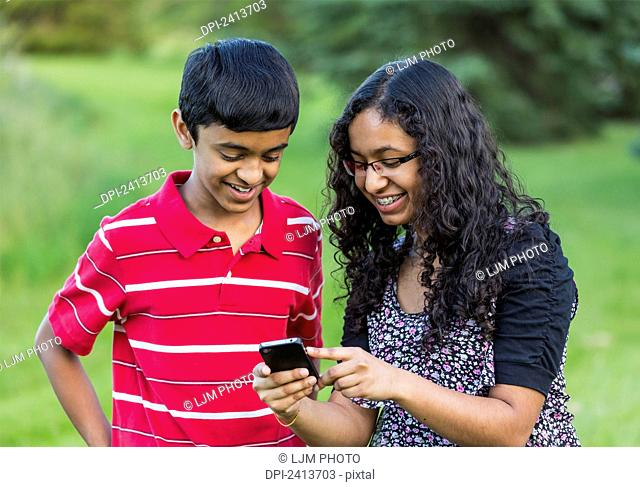 Brother and sister using social media on a smart phone; Edmonton, Alberta, Canada