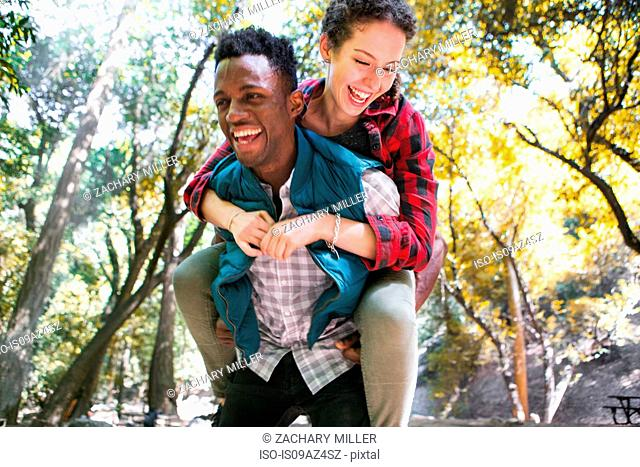 Young female hiker getting piggy back from boyfriend in forest, Arcadia, California, USA