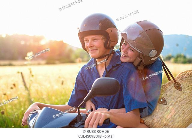 Romantic young couple riding moped on rural road, Majorca, Spain