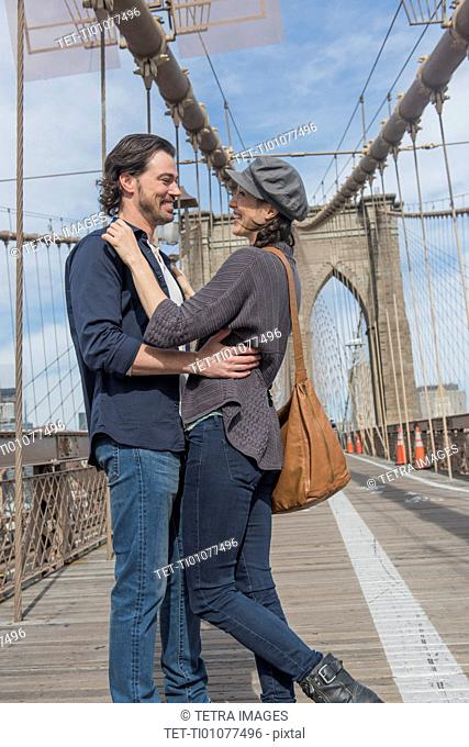 Happy couple embracing on Brooklyn Bridge