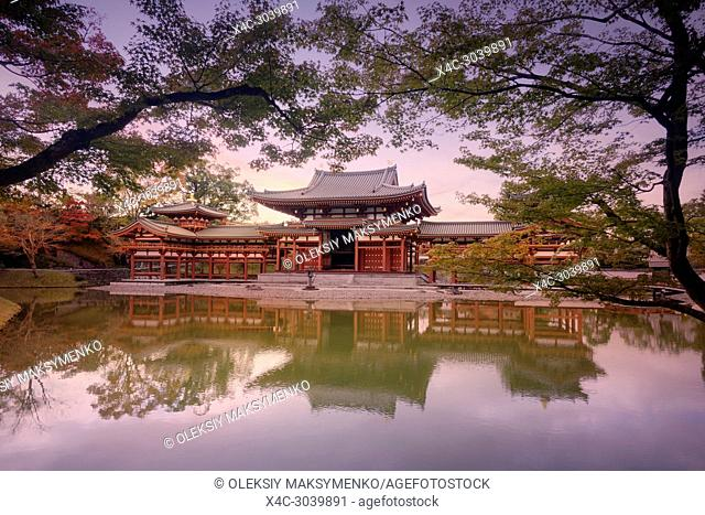 Phoenix Hall, Hoodo or Amida Hall, of Byodo-in, Jodo-shiki garden with a pond in a beautiful surreal sunrise autumn scenery framed by Japanese maple tree...