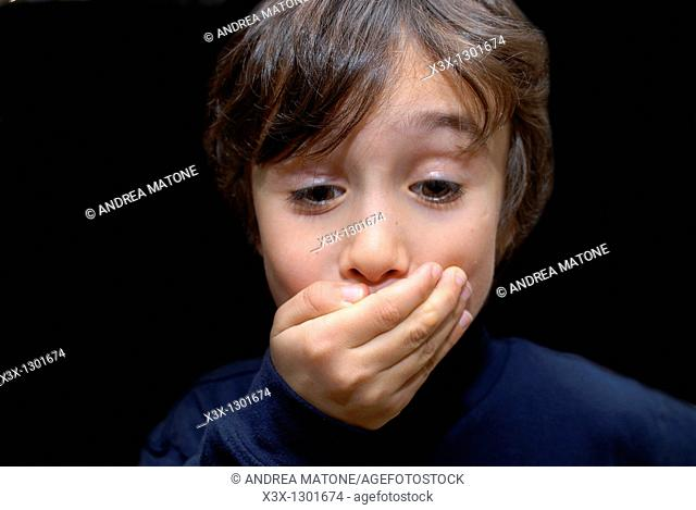 Male child keeping a secret with a hand over his mouth