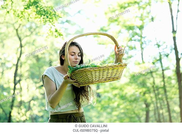 Young woman smelling foraged wild herbs in forest, Vogogna, Verbania, Piemonte, Italy