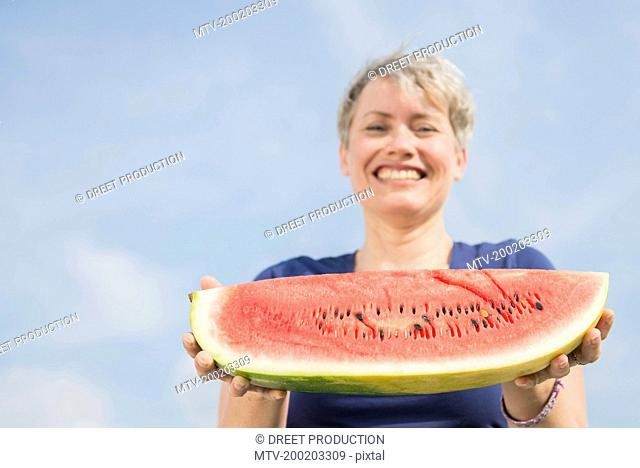 Portrait of mature woman holding watermelon, smiling