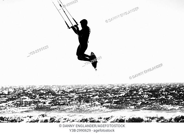 A silhouetted image of a kite surfer taking air over the Pacific Ocean in San Diego, California
