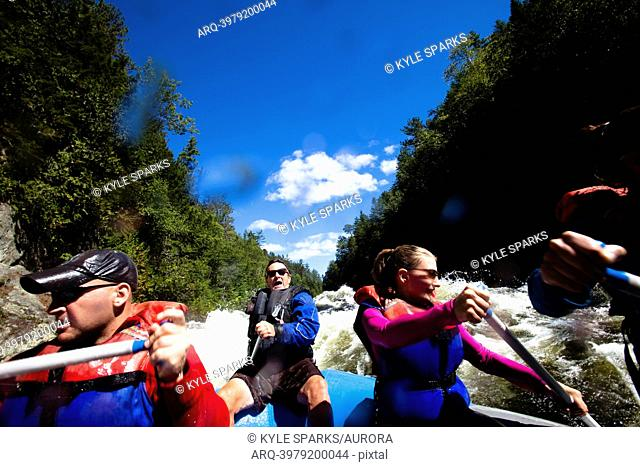 A group of adults whitewater rafting in Maine