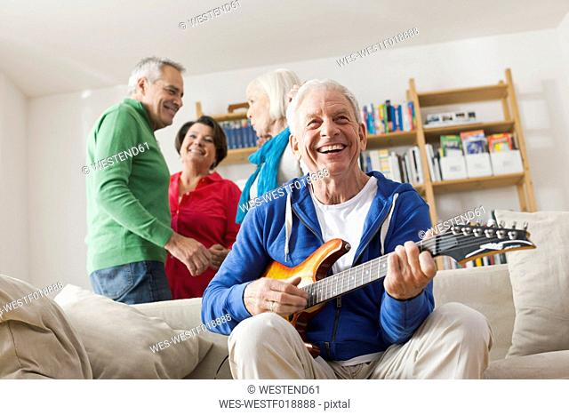 Germany, Leipzig, Senior man playing electric guitar, man and woman in background