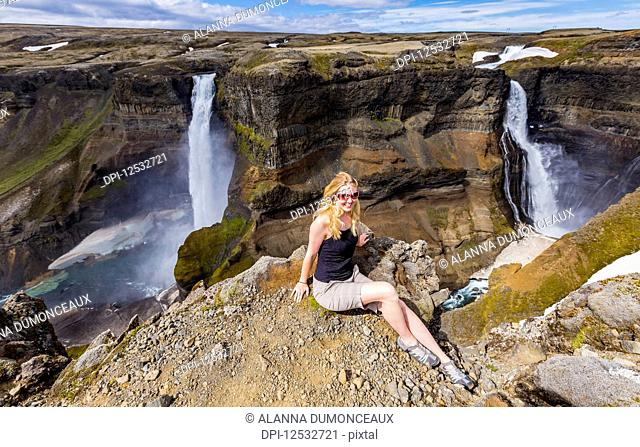 A young female hiker poses for a portrait on the edge of a stunning waterfall valley known as Haifoss, in Southern Iceland; Iceland