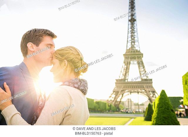 Caucasian couple kissing near Eiffel Tower, Paris, France