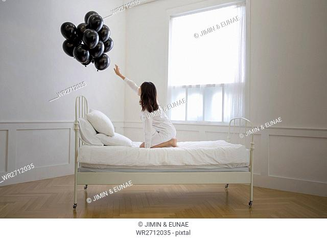 Young woman in bed reaching for black balloons