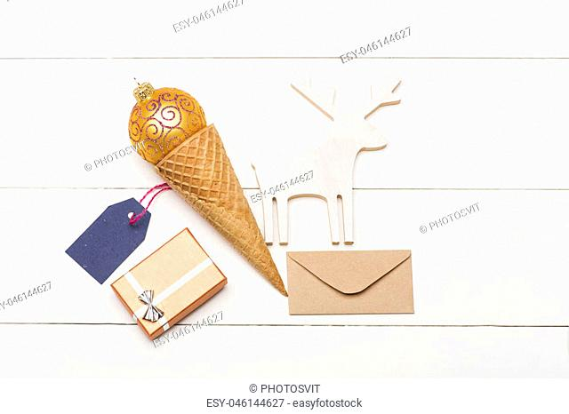 Colorful Christmas or New Year decoration with rose gold christmas ball, Christmas deer, ice cream cone, envelope, gift with silver bow